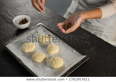 Woman adding dry fruits over unbaked cookie dough Stock photo © wavebreak_media