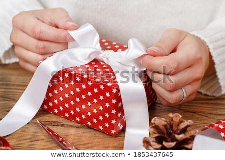 woman's hands tying up christmas gift box Stock photo © Lana_M