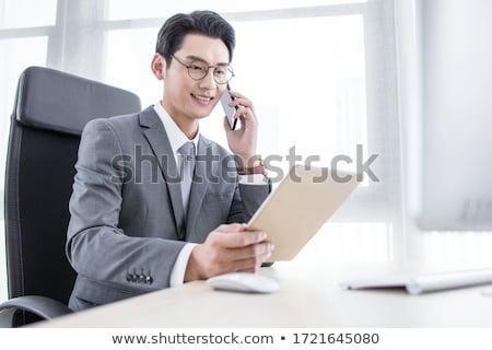 Asiático empresário falante telefone mesa de escritório computador Foto stock © studioworkstock