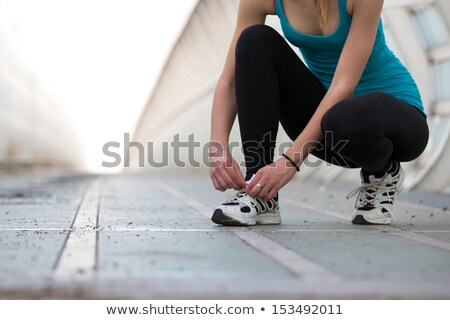 Woman tying her shoe laces before workout Stock photo © boggy