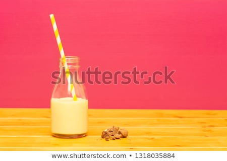 Milk bottle half full with banana milkshake with a straw Stock photo © sarahdoow