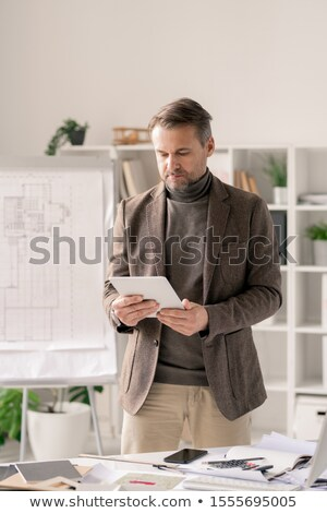 Confident architect in formalwear scrolling in tablet while standing by desk Stock photo © pressmaster