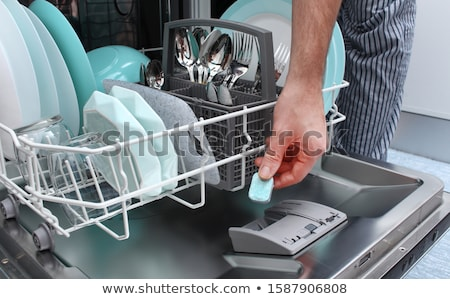 hand loads a dishwashing tablet into a dishwasher  Stock photo © simpson33