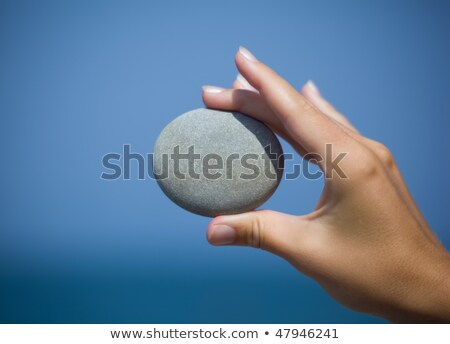female hand holding pebble against sea holds with side stock photo © paha_l