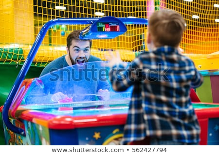 father and son playing air hockey game at amusement park stock photo © deandrobot
