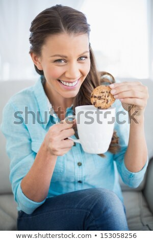 Woman dipping a cookie into a mug Stock photo © wavebreak_media