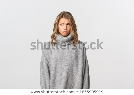 portrait of a sad upset girl in sweater standing stock photo © deandrobot