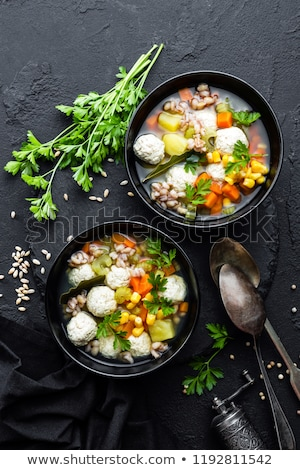 fresh vegetable soup with meatballs and pearl barley in bowl on black background top view stock photo © yelenayemchuk