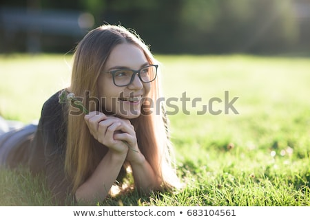 portrait of a cute young girl laying on a grass at the park stock photo © deandrobot
