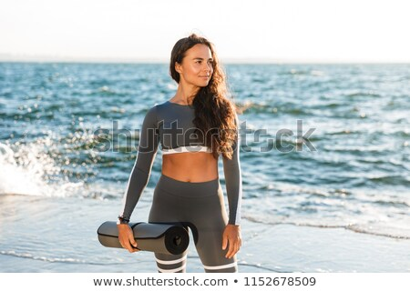 Happy young fitness lady holding fitness rug. Stock photo © deandrobot