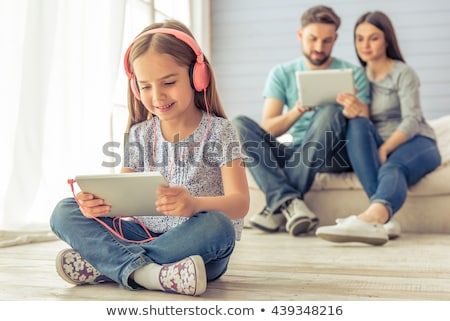 man sitting cross-legged in a sofa using a tablet Stock photo © nito