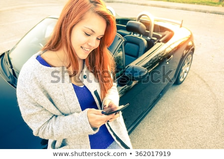 Young woman using mobile phone and standing by cabriolet car Stock photo © boggy