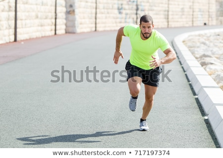 Handsome young strong sports man outdoors running Stock photo © deandrobot