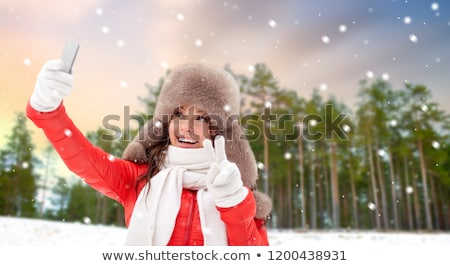 happy woman taking selfie over winter forest stock photo © dolgachov