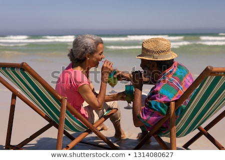 side view of senior couple relaxing on sun lounger and drinking cocktail on beach in the sunshine stock photo © wavebreak_media