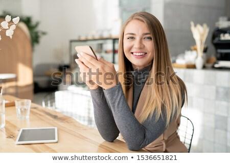 Csinos lány mosoly fogakkal néz sms chat okostelefon Stock fotó © pressmaster