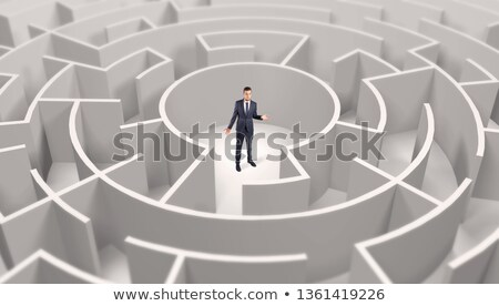 Businessman standing in a middle of a round maze Stock photo © ra2studio