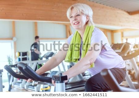 Idős nő testmozgás jobb fitnessz bicikli Stock fotó © Kzenon