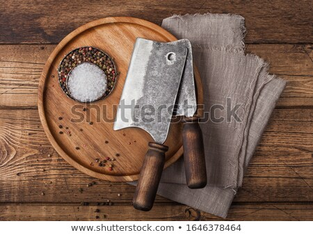 Vintage hatchets for meat on round wooden plate with salt and pepper on wooden table background with Stock photo © DenisMArt
