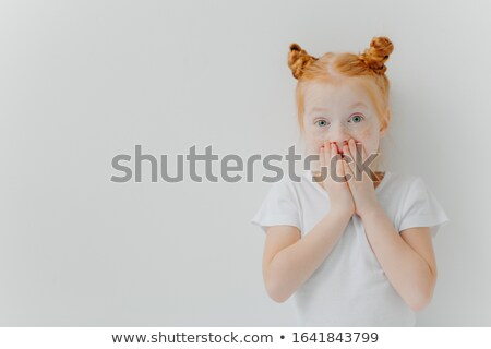Horizontal shot of surprised red head girl covers mouth, watches exciting cartoon, has unexpected re Stock photo © vkstudio