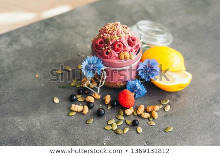 Delicious raspberry ice cream with pumpkin seeds and hempseed, decorated with blue cornflowers, blac Stock photo © vkstudio