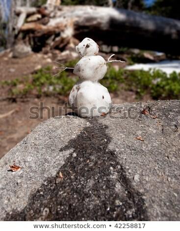 Melting snowman on granite rock Stock photo © backyardproductions