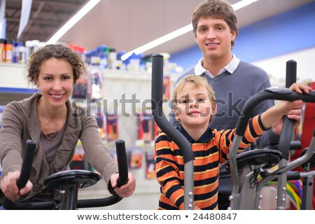 Young  woman on sports training apparatus in shop Stock photo © Paha_L