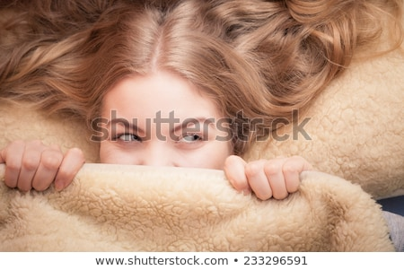 Young woman hiding under the bedclothes Stock photo © dash