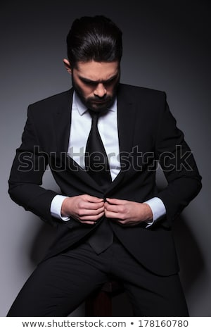 Fashion man looking down while sitting on a stool Stock photo © feedough