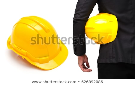 Male worker's hand holding yellow industrial protective helmet. Stock photo © stevanovicigor