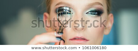 Woman using eye lash curler Stock photo © stockyimages