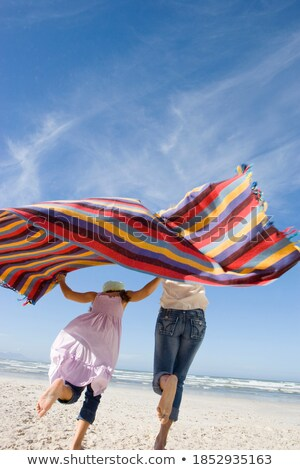 Girls running with blankets at beach Stock photo © IS2
