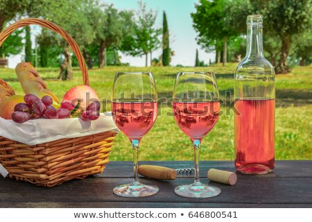 bottle and glasses of pink rose wine with cork and corkscrew opener on stone kitchen table backgroun stock photo © denismart