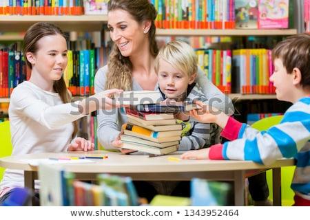 nő · olvas · könyv · könyvtár · asztal · diák - stock fotó © kzenon