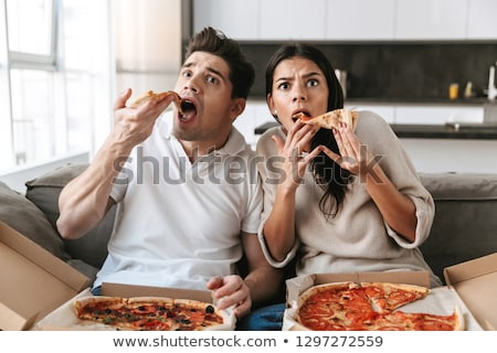 young couple enjoying eating pizza and watching tv stock photo © boggy