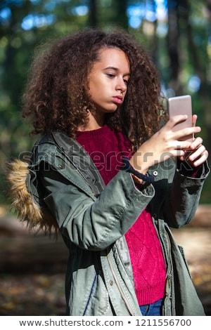 Kręcone włosy teen girl smartphone jesienią lasu portret Zdjęcia stock © boggy