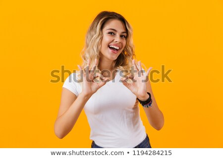 Photo of charming blond woman in basic clothing smiling and show Stock photo © deandrobot