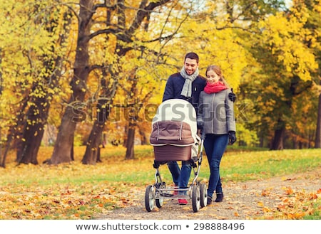happy couple walking together with pram autumn stock photo © robuart
