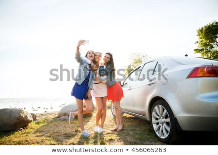 happy teenage girls or women near car at seaside Stock photo © dolgachov