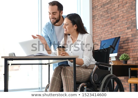 young male employee in wheelchair working in the office stock photo © elnur