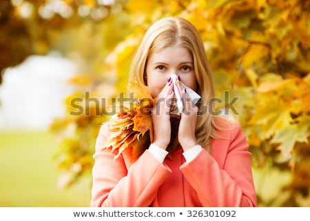 Young woman sneezes in the park against the background of a flowering tree. Allergy to pollen concep Stock photo © galitskaya