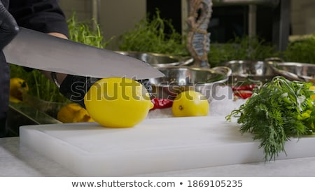 close up of chopped lemon and knife on table stock photo © dolgachov