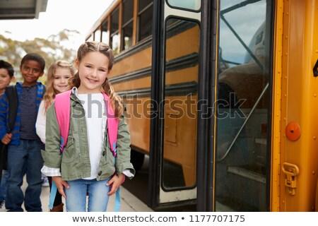 Trzy dziewcząt szkoły czeka autobus posiedzenia Zdjęcia stock © Kzenon