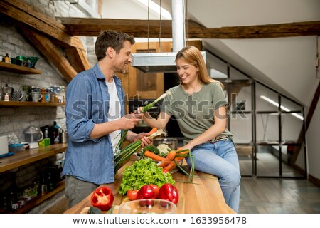 Trendy couple peeling and cutting vegetables from the market in  Stock photo © boggy