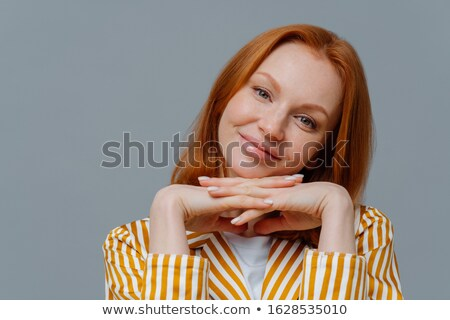Close up shot of attractive positive woman tilts head, keeps hands together near face, wears casual  Stock photo © vkstudio