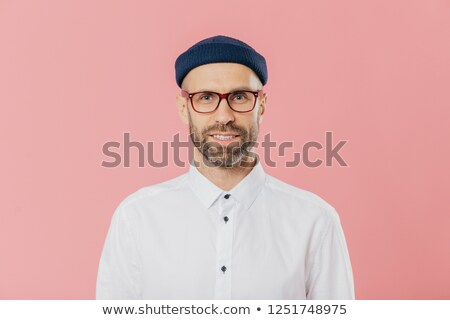 Headshot of satisfied bearded young man looks confidently at camera through spectacles, wears white  Stock photo © vkstudio