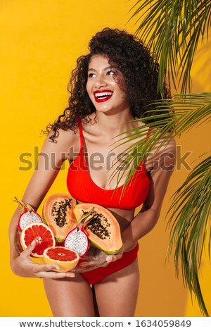 Cheery woman holding exotic fruit. Stock photo © deandrobot
