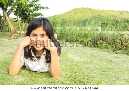 Beautiful young woman in flower garden sun tanning Stock photo © darrinhenry