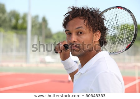 male tennis player holding racquet over shoulder during game on hard court stock photo © photography33