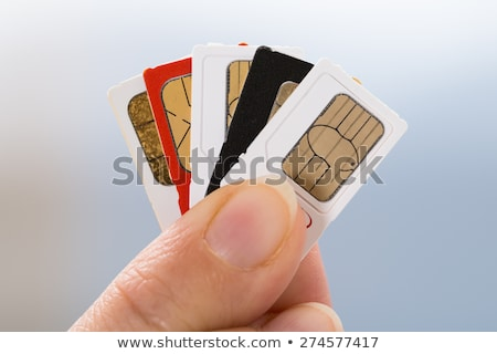 Fingers holding a mobile phone GSM SIM Card Stock photo © broker